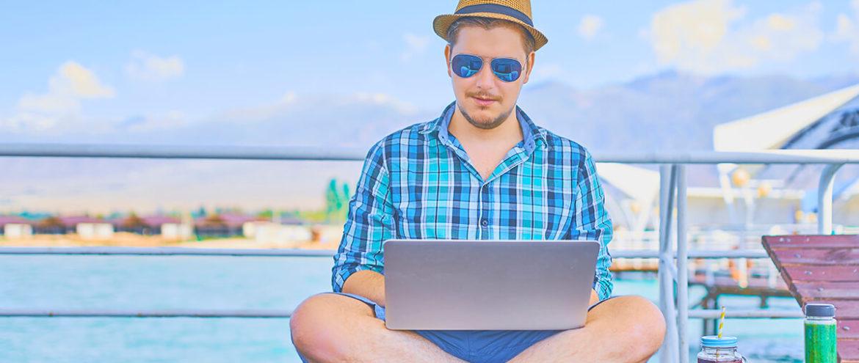 mężczyzna z komputerem na wakacjach